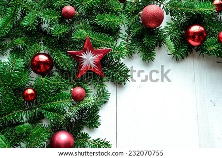 Red Christmas ornament balls with star on fir leaves.Image of Christmas