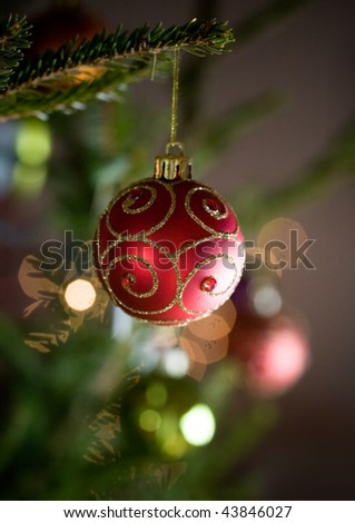 Red christmas ornament hanging from christmas tree - stock photo