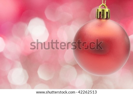 Red christmas ornament on red off focus illumination background