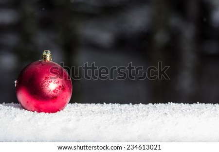 Red Christmas ornament on snow covered railing - stock photo