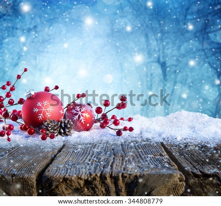 Red Christmas Ornament On Snowy Table With Snowfall On Background - stock photo