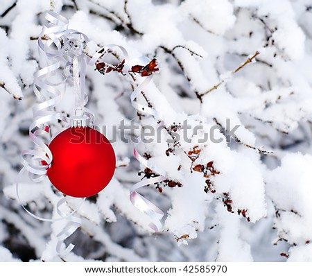 Red Christmas ornament on snowy tree - stock photo