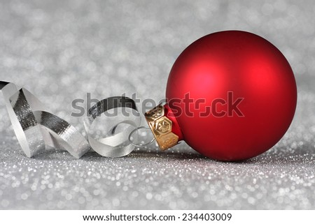 Red Christmas ornament with curled ribbon on a silver background - stock photo