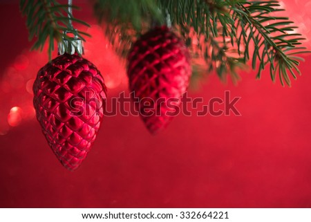 Red christmas ornaments (cones) on the xmas tree on red background isolated. Merry christmas card. Winter holidays. Xmas theme. Happy New Year. - stock photo