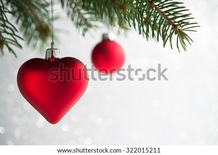 Red christmas ornaments (heart and ball) on the xmas tree on glitter bokeh background. Merry christmas card. Winter holidays. Xmas theme. - stock photo