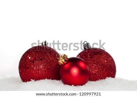 Red christmas ornaments laying on the snow - stock photo