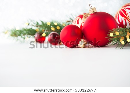 Red christmas ornaments on white background with xmas tree, twinkle bokeh lights. Merry christmas card. Winter holiday xmas theme. Happy New Year. Space for text.