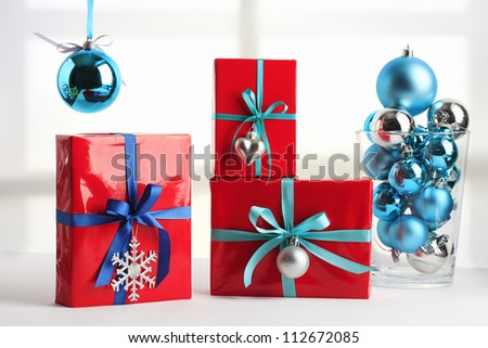 Red christmas present with blue ribbon and christmas spheres - stock photo