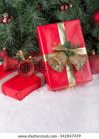 Red Christmas presents on snow under a holiday tree - stock photo