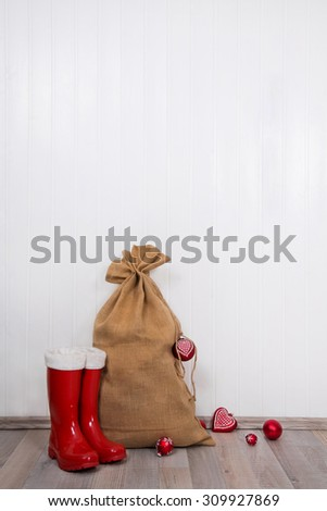 Red christmas presents with santa boots and sack on white wooden wall for decoration. - stock photo