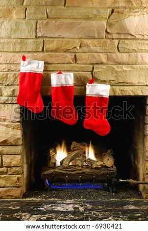 Red christmas stockings on fireplace - stock photo