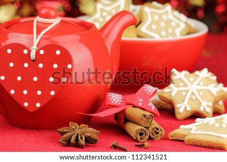 Red Christmas table setting with teapot and gingerbread cookies - stock photo