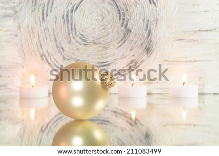 red christmas tree ball on mirror in front of an abstract background - stock photo