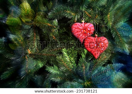 Red Christmas tree decoration in the form of heart on a fir-tree branch - stock photo