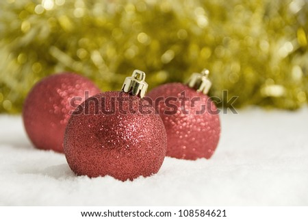 Red Christmas Tree Decorations and Gold Tinsel in Snow - stock photo