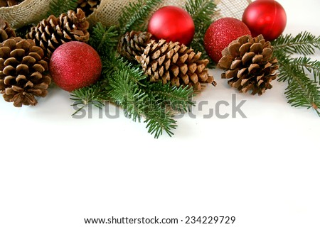 Red Christmas Tree ornaments, natural pine cones, evergreen branches, and burlap holiday ribbon fabric are creating a decorative top border, isolated on a blank white background for copy-space. - stock photo