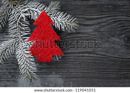 Red Christmas tree with frosted fir branch on wood - stock photo