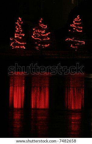 Red christmas trees reflecting off of icy lake - stock photo