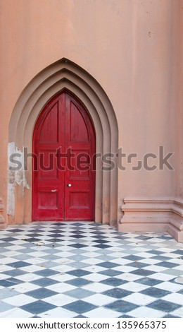 Red church door beyond black and white checkerboard floor with white doorknob - stock photo