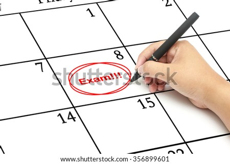 Red circle.Mark on the calendar with  words Exam written on a calendar to remind you an important appointment - stock photo