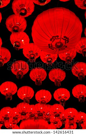Red, circular Chinese lanterns creating repetitive circular pattern on black background. - stock photo