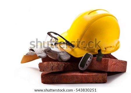 Red clay bricks, yellow hard hat, goggles and gloves on a white background
