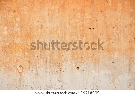 Red clay stained on the white exposed crack concrete wall. - stock photo