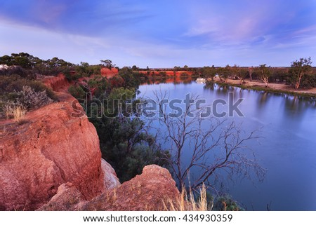 Red cliffs of Murray river on the border between Victoria and New South Wales states of Australia. Elevated red bank of the river overlooks river bend with cruise ship at sunset. - stock photo