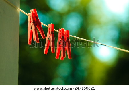 Red clips for washing laundry clothes pegs on string rope outdoor. Housework concept. - stock photo