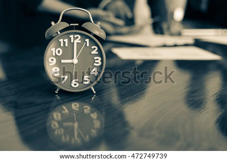Red clock for business time on wooden desk in business room.Business time concept.Monotone style.
