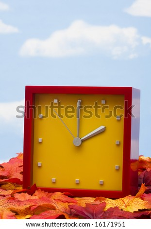 Red clock on fall leaves â?? the time change in the fall