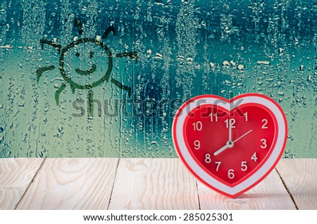red clock on rain drop and sun sign glass window background