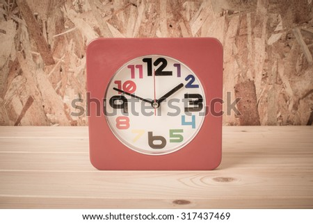 Red clock on wood table, vintage color background