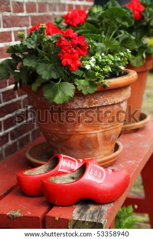 red clogs with flowers on bench - stock photo