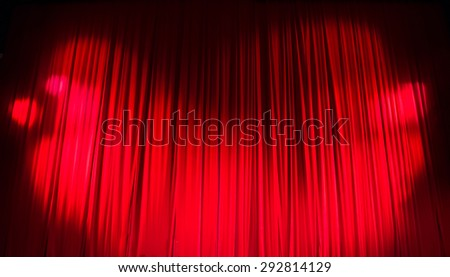 Red closed curtain with light spots in a theater. - stock photo
