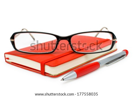 Red closed paper notepad, glasses and pen isolated on white background - stock photo