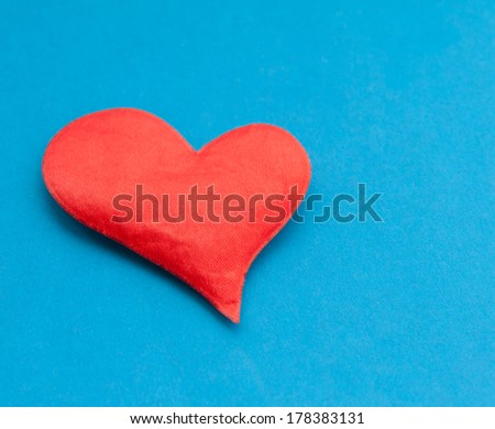 Red cloth heart on blue paper background. Selective focus.