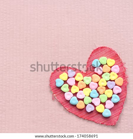 Red Cloth Valentine with Heart Shaped Candies in the center of it, all on a pink cardboard background with room or space for copy, text, words - stock photo
