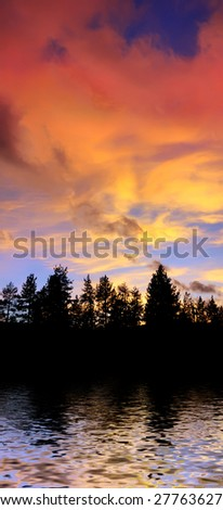 red clouds at sunset above tree silhouettes reflecting in the water on the Lake Tahoe California - stock photo