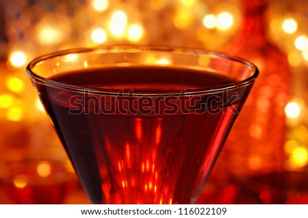 Red cocktail drink on bar with a bottle and defocused golden lights in background. Macro with extremely shallow dof. - stock photo