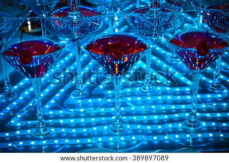 Red cocktail in Martini glasses decorated with cherries on a background with blue neon lighting - stock photo