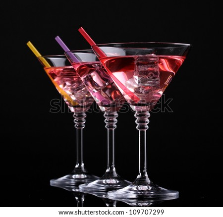 Red cocktail in martini glasses isolated on black - stock photo