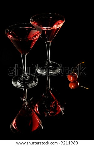 Red cocktail in martini glasses on black - stock photo