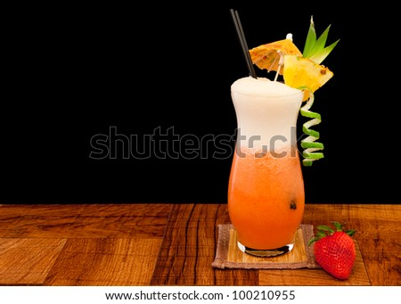 red cocktail isolated o na black background garnished with a lime twist and a fresh pineapple slice - stock photo