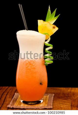 red cocktail isolated on a black background garnished with a lime twist and a fresh pineapple slice - stock photo