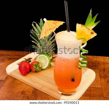red cocktail isolated ona black background garnished with a lime twist and a fresh pineapple slice - stock photo