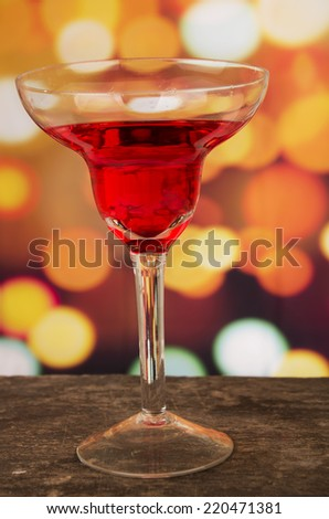 red cocktail on a wooden table with party lights in the background