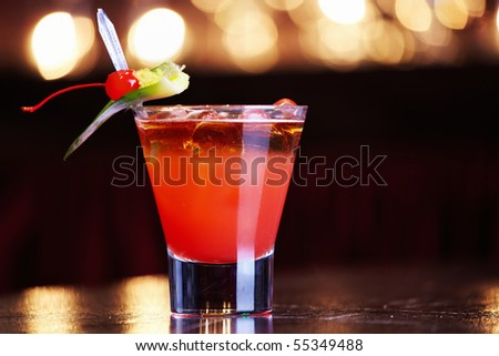 Red cocktail with ice and a cherry - stock photo