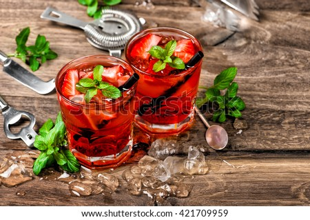 Red cocktail with ice, mint leaves and strawberry. Alcoholic and non alcoholic drinks making bar tools. Vintage style toned photo - stock photo