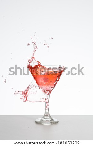 Red cocktail with ice splash - stock photo